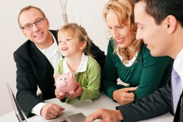 family with girl holding piggy bank looking at laptop
